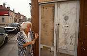 Walking past a boarded-up shop on a Liverpool street corner, a middle-aged woman passes graffiti scrawled by local youths on the doors. The scene is of a poor area needing investment but this is an area of the city known for high crime and areas of dereliction where the community are treated as second class citizens.