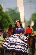 "Riders, men and women dress up in their finery, the traditional ""traje corto"" (short jacket, tight trousers and boots) for men and the ""faralaes"" or ""trajes de flamenca"" (flamenco style dress) for women. The men traditionally wear hats called ""cordobés""...The Feria de abril de Sevilla, ""Seville April Fair"" dates back to 1847. During the 1920s, the feria reached its peak and became the spectacle that it is today. It is held in the Andalusian capital of Seville in Spain. The fair generally begins two weeks after the Semana Santa, Easter Holy Week. The fair officially begins at midnight on Monday, and runs six days, ending on the following Sunday. Each day the fiesta begins with the parade of carriages and riders, at midday, carrying Seville's citizens to the bullring, La Real Maestranza...For the duration of the fair, the fairgrounds and a vast area on the far bank of the Guadalquivir River are covered in rows of casetas (individual decorated marquee tents which are temporarily built on the fairground). Some of these casetas belong to the prominent families of Seville, some to groups of friends, clubs, trade associations or political parties. From around nine at night until six or seven the following morning, at first in the streets and later only within each caseta, crowds of people party and dance Sevillanas, traditional Flamenco dances, Sevillan style drinking Jerez sherry, or Manzanilla wine, and eating tapas."