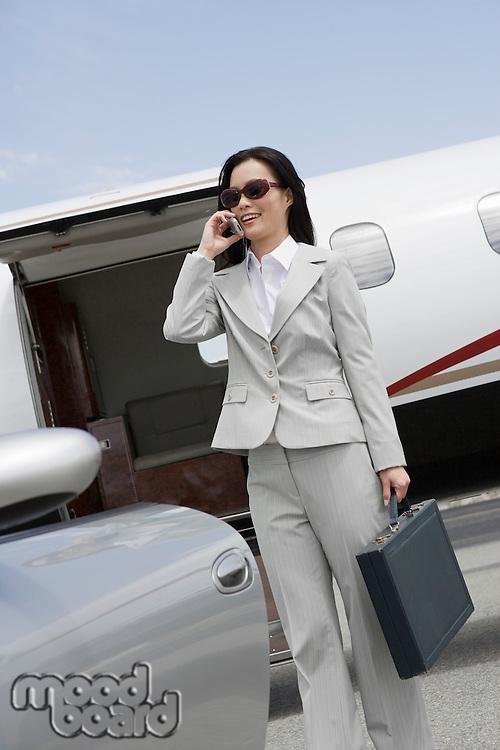 Mid-adult businesswoman using mobile phone in front of airplane and car.
