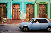 HAVANA, CUBA - CIRCA MARCH 2017: Old car drives in the streets of Havana, passing by a colorful home.