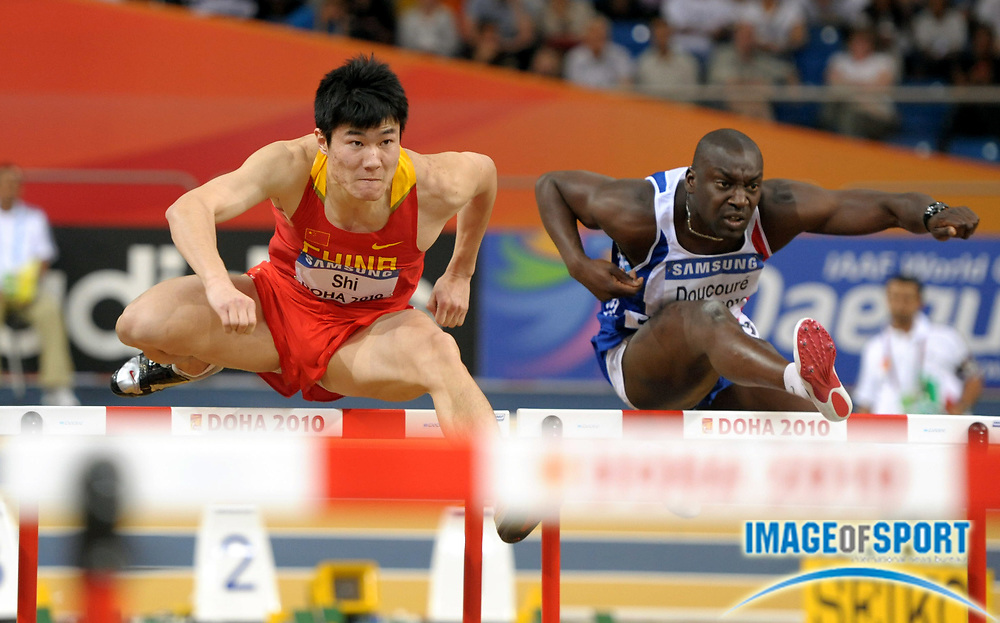 Mar 12, 2010; Doha, QATAR; Dongpeng Shi (CHN), left, and Ladji Doucoure (FRA) compete in a 60m hurdle heat in the IAAF World Indoor Championships in Athletics at the Aspire Dome. Shi finished fourth in 7.83 to advance to the semifinals.