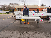 """11 APRIL 2020 - DES MOINES, IOWA: JORDON ELWELL, owner and CEO of Midwest Foods, waits for a motorist during a food distribution in Des Moines. He used a plastic table to pass a ready to cook pasta meal to motorists as they drove past him. Most non-essential businesses in Iowa are closed until 30 April. Because of business closings causes by the Novel Coronavirus (SARS-CoV-2) pandemic, well over 100,000 Iowans filed first time claims for unemployment in the last three weeks, more than applied during the peak of the Great Recession of 2008. Local food banks have seen an unprecedented spike in people seeking nutritional assistance. Midwest Foods, a Des Moines based company and owner of Ginos Fine Italian Foods, gave away 1,000 complete dinners with sauce, noodles, salad, and dressing Saturday morning. People started lining up 3 hours before the food distribution began. The food distribution was done following """"social distancing"""" guidelines and all of the workers wore masks and gloves.       PHOTO BY JACK KURTZ"""