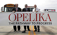 The City of Opelika officially opened Dunlop Drive on Friday.  The new road and bridge were constructed to replace the Priester Street bridge, which was impassable by service vehichles such as school buses, firetrucks, and ambulances.  City Council president Jerry Teel, Opelika mayor Gary Fuller, and Dr. Bill Lazenby stand behind a ceremonial sign before the ribbon cutting.  Fuller reminded those present that even though the new road was smooth, the speed limit was still 35 miles an hour.  Photo by Elliot Knight