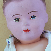 Head and chest of vintage boy doll with pink face and brown-pink body and wearing shirt in macho manner