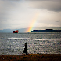 A silhouetted woman walking along the beach with a ship and a rainbow off in the background.