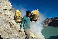Indonesie. Île de Java. Cratère du volcan Kawah Ijen à envion 2500m d'altitude. Les forçat du soufre. Un des dernier endroit au monde où des hommes travaillent à mains nues. Ils transportent 70kg de soufre dans leur panier pour le vendre aux industries sucières. // Indonesia. Java island. Mining Sulfur by Hand in Kawah Ijen Volcano around 2500m alt. Men working inside Kawah Ijen volcano, in East Java, one of the last places in the world where people mine sulfur by hand, carrying it out of the volcano in wicker baskets (70kg) to a collection point below where factories purchase the yellow sulfur stones to use in manufacturing.<br />