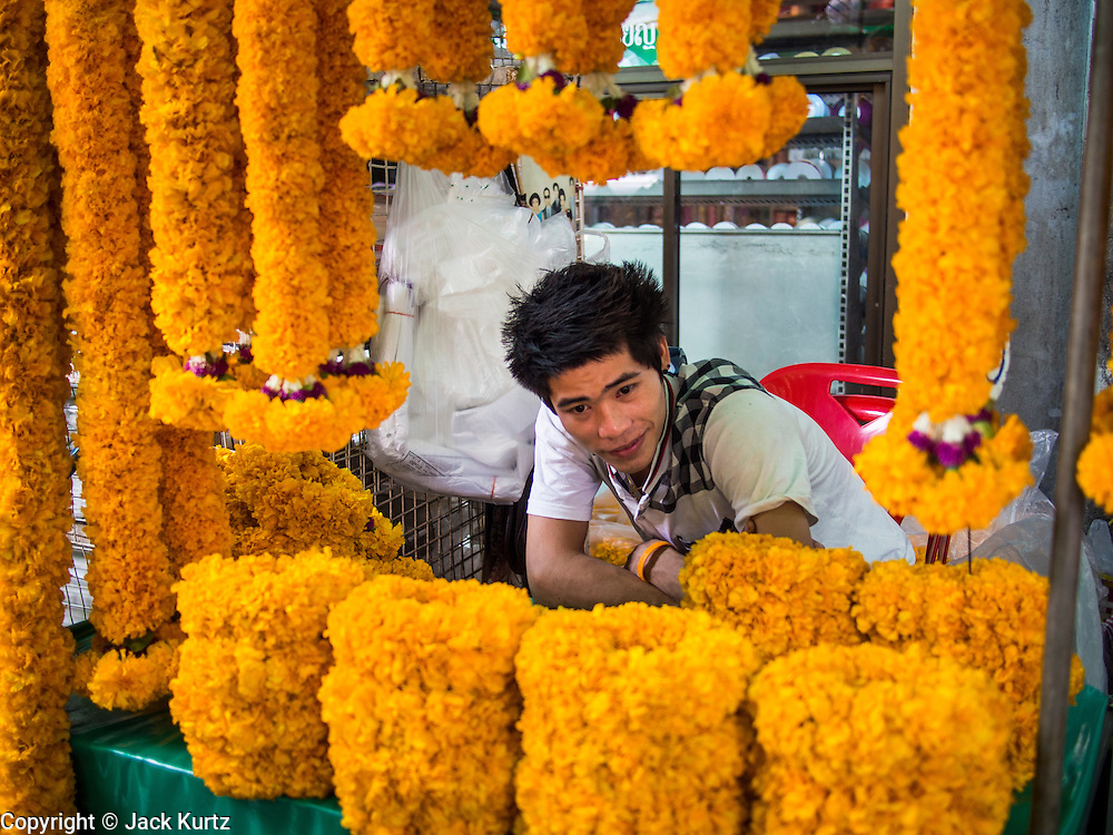 "23 AUGUST 2013 - BANGKOK, THAILAND:    A vendor sells marigold flower garlands in Pak Khlong Talad in Bangkok. Thailand entered a ""technical"" recession this month after the economy shrank by 0.3% in the second quarter of the year. The 0.3% contraction in gross domestic product between April and June followed a previous fall of 1.7% during the first quarter of 2013. The contraction is being blamed on a drop in demand for exports, a drop in domestic demand and a loss of consumer confidence. At the same time, the value of the Thai Baht against the US Dollar has dropped significantly, from a high of about 28Baht to $1 in April to 32THB to 1USD in August.    PHOTO BY JACK KURTZ"
