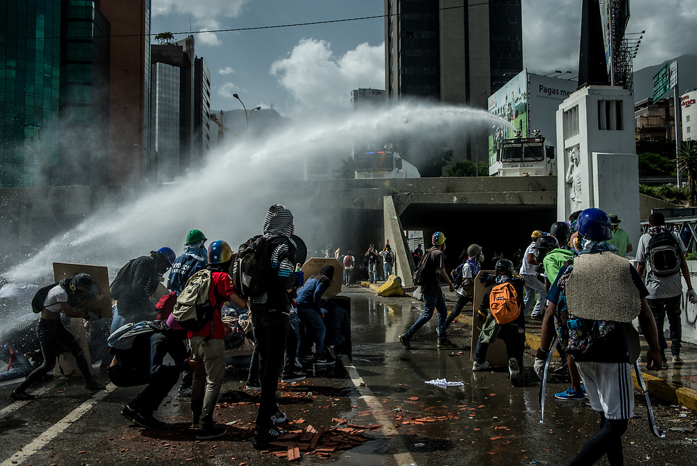 CARACAS, VENEZUELA - MAY 26, 2017:  Anti-government protesters take cover behind homemade shields as National Guard soldiers fire a water cannon at them. The streets of Caracas and other cities across Venezuela have been filled with tens of thousands of demonstrators for nearly 100 days of massive protests, held since April 1st. Protesters are enraged at the government for becoming an increasingly repressive, authoritarian regime that has delayed elections, used armed government loyalist to threaten dissidents, called for the Constitution to be re-written to favor them, jailed and tortured protesters and members of the political opposition, and whose corruption and failed economic policy has caused the current economic crisis that has led to widespread food and medicine shortages across the country.  Independent local media report nearly 100 people have been killed during protests and protest-related riots and looting.  The government currently only officially reports 75 deaths.  Over 2,000 people have been injured, and over 3,000 protesters have been detained by authorities.  PHOTO: Meridith Kohut