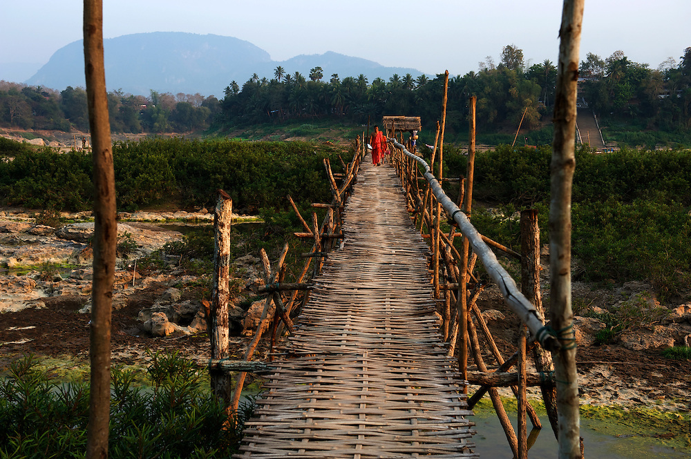 Novice monks cross the sandbanks of the Mekong River during the dry season using bamboo bridges.