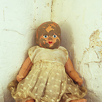 Antique doll in soiled white lacy dress with painted staring blue eyes and red lips but most of her pink flesh paint cracked off sitting on ledge in corner