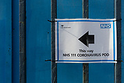 An NHS sign points towards a Coronavirus testing pod outside the A&E Department of Kings College Hospital in Camberwell, south London, on 11th March 2020, in London, England.