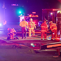 Gallup firefighters gather on Maloney Avenue after extinguishing a blaze near Third Street in Gallup Monday.