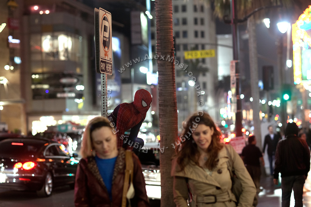 A person dressed as Spiderman is crouched on a parking meter along Hollywood Boulevard, in central Los Angeles, California, USA.