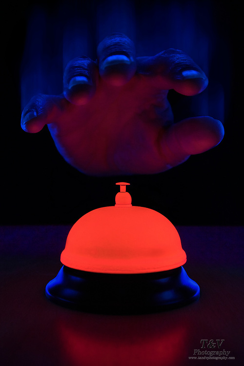 A hand about to ring a glowing service bell. Blacklight photography.