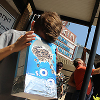 RAY VAN DUSEN/BUY AT PHOTOS.MONROECOUNTYJOURNAL.COM<br /> Seth Terry of Aberdeen Watches the partial eclipse just before its 1:27 p.m. peak downtown. A dark hue during the eclipse was enough to trigger the LED street lights underneath the Main Street awnings.