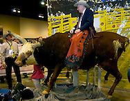 Omaha, Neb 5/6/06 Warren Buffet sits atop a bull at the Justin Boots booth on the floor at the Berkshire Hathaway annual meeting in the Qwest Center Omaha Saturday Morning..(Chris Machian/For Bloomberg)