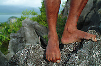 A detail view of a Papuan's bare feet curled around sharp limestone karst testifies to the hardiness of Raja Ampat's indigenous people. Travel photography by Djuna Ivereigh.