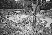 French guiana, dorlin, inini.<br /> <br /> Exploitation aurifere. La terre est retournee et lavee a la recherche de paillettes qui seront amalgamees par addition de mercure. Christiane TAUBIRA, depute de Guyane, publie un rapport : &laquo; Si l'on prend en compte les couts environnementaux, sanitaires et sociaux engendres par cette activite, on peut s'interroger sur la valeur ajoutee creee par l'activite aurifere&hellip; La ou il n'y a pas moyen de faire autre chose, on ne va pas dire aux gens : crevez de faim ou allez emarger au RMI &raquo;. Les orpailleurs du Syndicat Minier de l&rsquo;Ouest Guyanais, soulignent que l&rsquo;activite aurifere est le seul secteur productif capable d&rsquo;absorber une main d&rsquo;&oelig;uvre abondante et peu formee. Elle permet a la population de ne plus dependre du versement des diverses prestations sociales qui constituent l&rsquo;essentiel des revenus des familles. Les efforts entrepris par certains pour assainir et moderniser la profession se heurtent pourtant aux limites de la legalite.