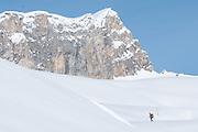 Schneeschuhwanderer allein auf Tour<br /> <br /> Lonely snowshoe hiker underneath a large rockwall