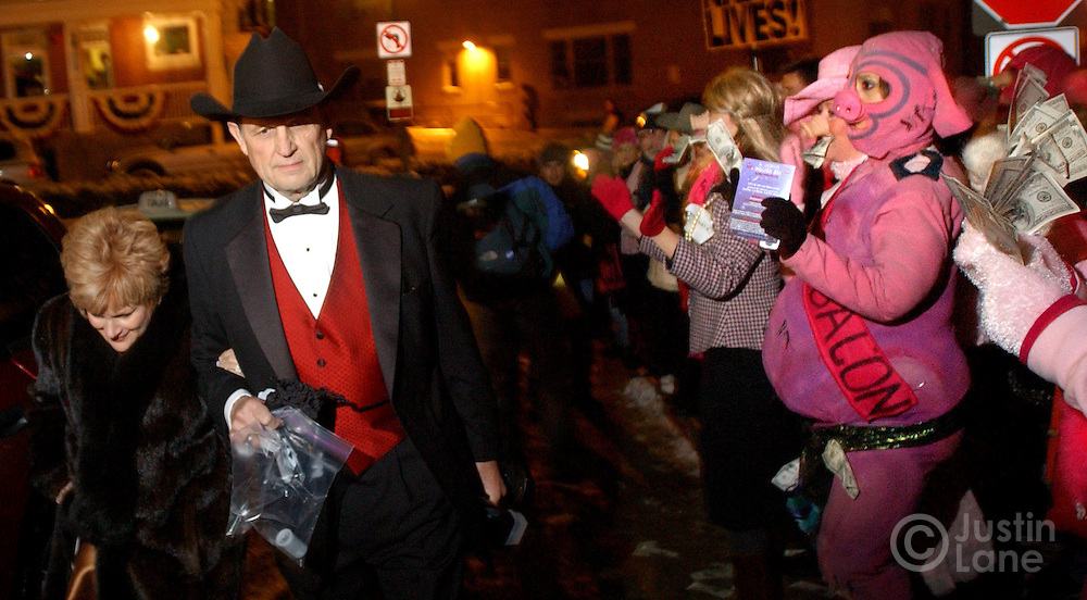 A protestor dressed as a pig (R) heckles two guests (L) arriving for the Black Tie and Boots Inaugural Ball at a Marriott hotel in Washington DC where Republicans were gathering for a celebration and an appearance by United States President George W. Bush Wednesday 19 January 2005.