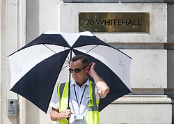 © Licensed to London News Pictures. 06/08/2018. London, UK. A security guard shelters form the sun underneath an umbrella outside the Home Office on Whitehall, Westminster, as hot weather continues in the capital. Photo credit: Ben Cawthra/LNP