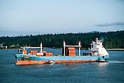 Cargo ship being guided into harbor by tugboats, Vancouver, British Columbia, Canada