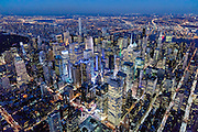 Aerial view of Midtown New York City at dusk, photographed from a helicopter near Hudson Yards, showing the New York Times Building at center bottom.