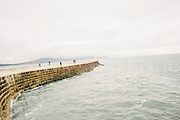 "Visitors watching the seascape at the harbour wall, known as ""The Cobb"". The wall features in Jane Austen's novel Persuasion, and in The French Lieutenant's Woman, a novel by British writer John Fowles, as well as the 1981 film of the same name, which was partly filmed in Lyme Regis."