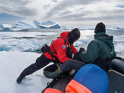 Wind-driven ice blocks our Zodiac boat, requiring pushing to free our path in the Southern Ocean offshore from Graham Land, the north part of the Antarctic Peninsula, Antarctica. One could easily get stuck for hours under difficult conditions.