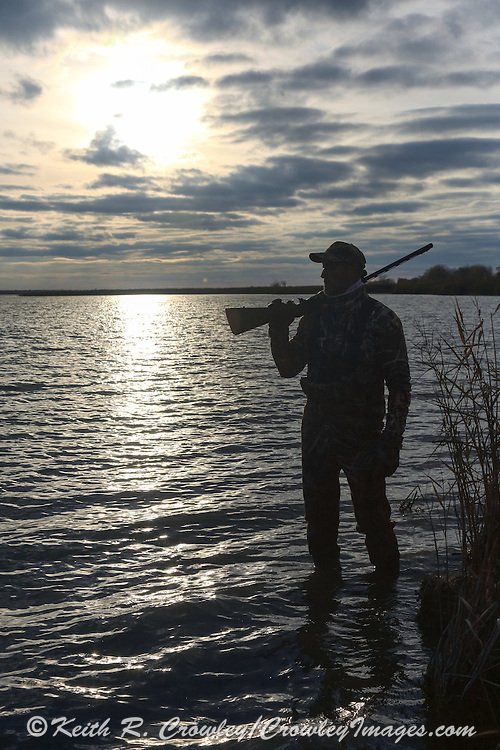 A hunter watches for ducks on a shallow marsh.