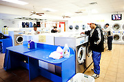 Roberto Barajas checks the detergent at Coin Laundry in East Point, as his son Eduardo (second from left) does the same, Georgia December 30, 2009. Monica, Roberto's wife, has been separated from her husband and son so she can continue dialysis in Mexico.