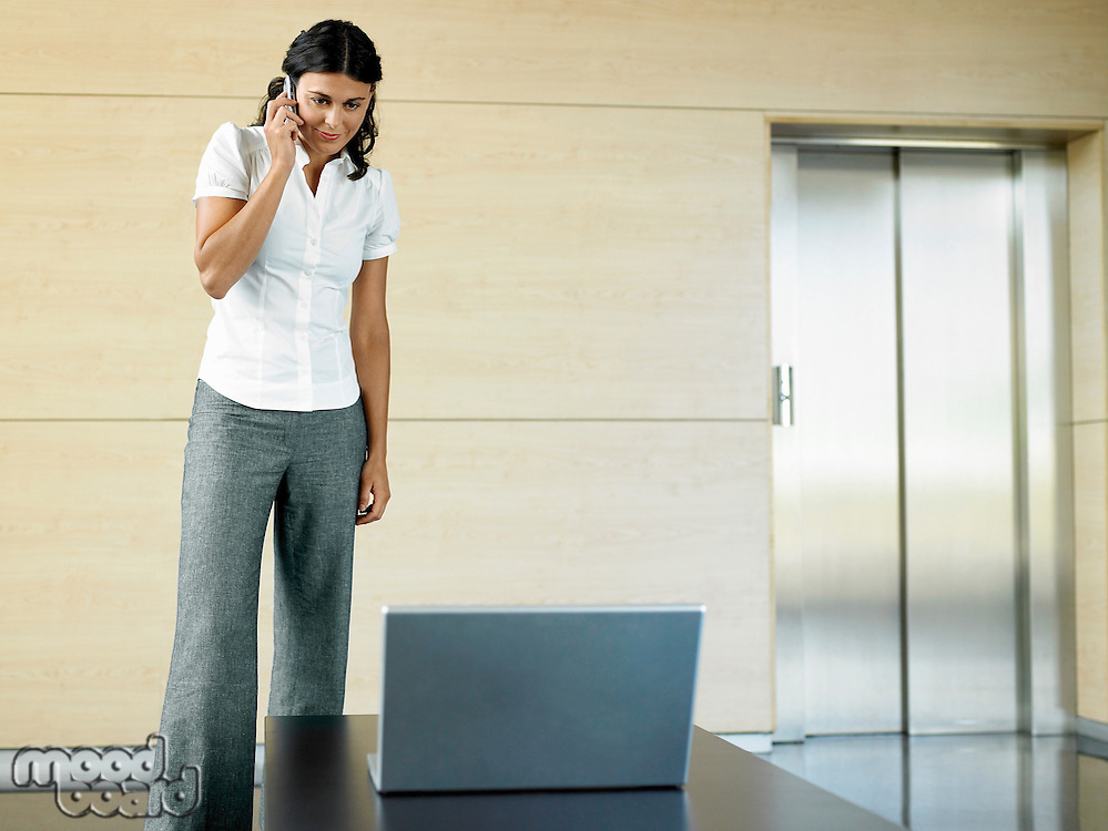 Office worker standing in lobby by laptop using cell phone