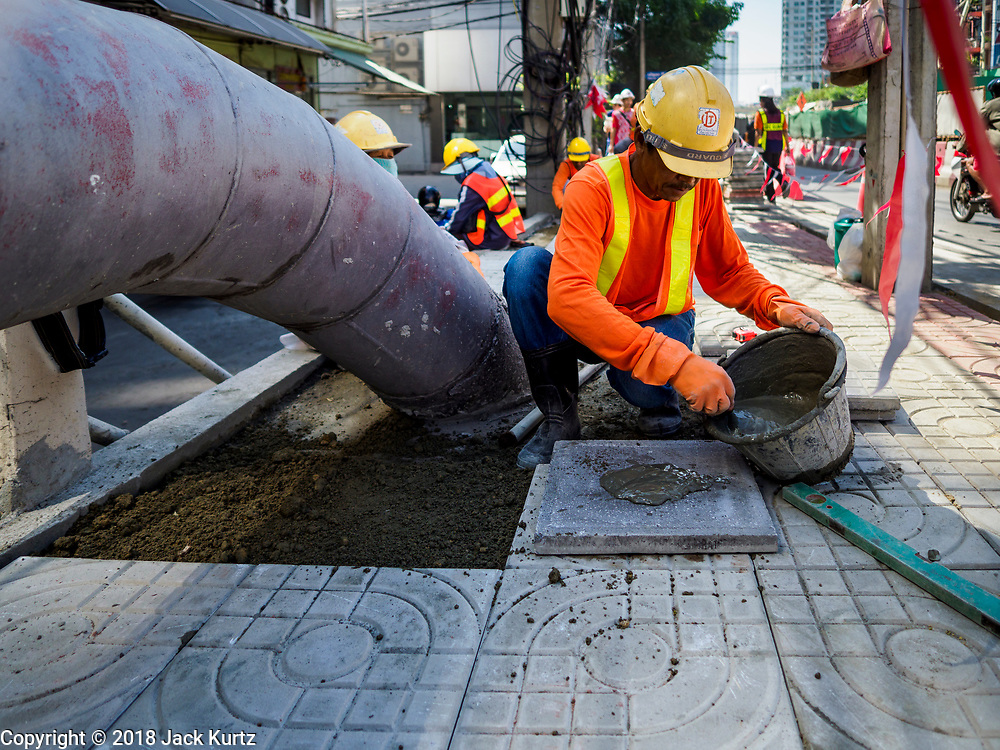 02 NOVEMBER 2018 - BANGKOK, THAILAND: A worker installs cement tiles on the sidewalk in front of the ICONSIAM development, which is scheduled to open November 9. ICONSIAM is a mixed-use development on the Thonburi side of the Chao Phraya River. It will include two large malls, with more than 520,000 square meters of retail space, an amusement park, two residential towers and a riverside park. It is the first large scale high end development on the Thonburi side of the river and will feature the first Apple Store in Thailand and the first Takashimaya department store in Thailand.    PHOTO BY JACK KURTZ