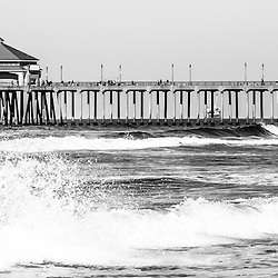 Huntington Beach Pier black and white panoramic picture. Panorama photo ratio is 1:3. Huntington Beach Pier is a registered historic place and has a Ruby's Restaurant at the end. Huntington Beach is a seaside beach city along the Pacific Ocean in Orange County Southern California and is also known as Surf City USA.