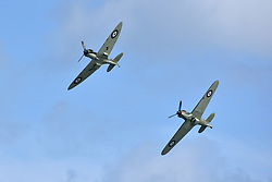 © Licensed to London News Pictures.  03/06/2017; Torbay, Devon, UK. Battle of Britain Memorial flight of a Spitfire and a Hurricane at the Torbay Airshow 2017. The 2017 Torbay Airshow returns this weekend on Saturday 3 and Sunday 4 June with an action packed programme of world class air displays. The world's premier aerobatic team The Red Arrows will be debuting a new routine in the first display of their season, featuring their trademark combination of close formations and precision flying. The full display programme for the weekend begins on the Saturday between 2-3pm with The Tigers Freefall Parachute Display Team, Team Raven Aerobatic Display Team, the Percival Piston Provost and the Strikemaster. From 3-4pm will be the highly anticipated display by the Red Arrows, former British Female Aerobatic Champion Lauren Richardson in her Pitts Special S1-S and world aerobatic competitor Gerald Cooper in his Xtreme XA41. Finishing off the action packed afternoon from 4-5pm will see displays from the AutoGyro, the Battle of Britain Memorial Flight aircraft, the PBY5A Catalina seaplane, The Blades and the Royal Air Force's Typhoon FGR4. Sunday afternoon will see each of the aircraft take to the skies again before the weekend closes with a final display from the RAF Chinook team. The two day show, which had its inaugural event last year, takes place on Paignton Green with the Bay providing a stunning natural amphitheatre for viewing the air displays and the perfect location for a large coastal airshow event. To stay up to date with the latest Torbay Airshow news and updates follow @torbayairshow on Facebook, Twitter and Instagram or visit www.torbayairshow.com. Picture credit : Simon Chapman/LNP