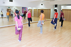 Group of adults taking part in aerobics class at their leisure sports centre,