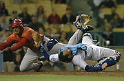Angel Nick Gorneault collides with Dodger Catcher Mike Lieberthal in the 8th inning.  The throw was late, and the collision allowed Gorneault to score in the 8th inning.The action was during the freeway series pre-season game at Dodger Stadium in Los Angeles, California on March 29, 2007. (John McCoy/Staff Photographer)