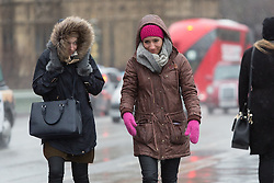 © Licensed to London News Pictures. 03/01/2016. London, UK. Two women walk in central London during wet and windy weather.   London and the UK has experienced heavy rain and wind today. Photo credit : Vickie Flores/LNP