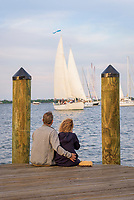 A couple embraces as a sailboat makes its way into harbor, City Dock, Annapolis, Maryland