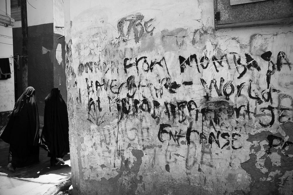 Old Town, Mombasa, Kenya. 2010<br /> <br /> Women walk past a graffiti wall in Mombasa, Kenya