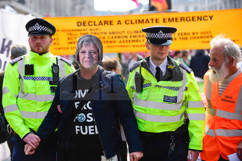 """© Licensed to London News Pictures. 17/04/2019. LONDON, UK.  Police officers arrest a protester, who is wearing a Thresa May face mask, at Oxford Circus during """"London: International Rebellion"""", on day three of a protest organised by Extinction Rebellion, demanding that governments take action against climate change.  Marble Arch, Oxford Circus, Piccadilly Circus, Waterloo Bridge and Parliament Square have been blocked by activists in the last three days.  Police have issued a section 14 order requiring protesters to convene at Marble Arch only so that the protest can continue.  Photo credit: Stephen Chung/LNP"""