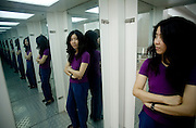 "Chinese artist  Yin Xiuzhen poses in a cubicle with many mirrors, an installation, part of a project called ""Trendy Terrorism; I cannot promise anything for the future."""