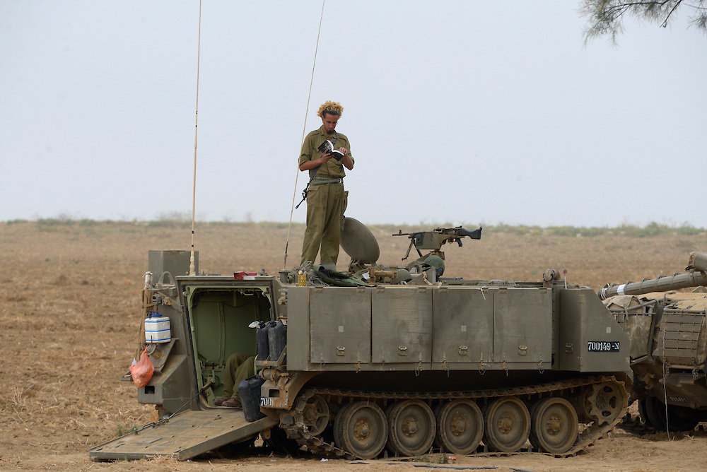An IDF soldier reads a book atop of an APC in Southern Israel near the border with Gaza, on the 4'th day of Operation Protective Edge, July 11, 2014. As Israel prepares for a wider operation, Gaza militants continue firing into Southern and central Israel. Photo by Gili Yaari