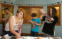 Lili Griggs, Keegan Ridings and Jack Brown add some fresh blood to their flesh wounds created in the Zombie Workshop at Gilford Library Thursday afternoon.  (Karen Bobotas/for the Laconia Daily Sun)