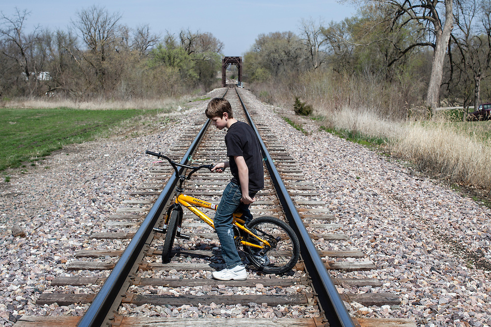 Joe McFarland rides his bicycle along train tracks on Sunday, March 25, 2012 in Webster City, IA.