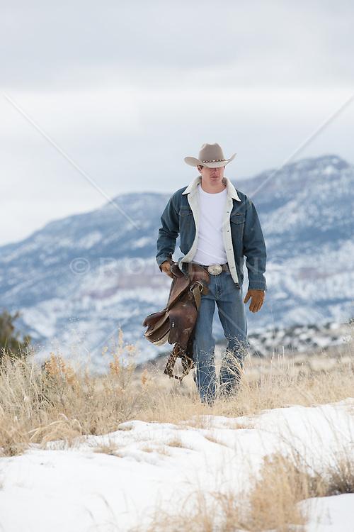rugged cowboy carrying a saddle through a snowy mountain range
