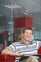 Male office worker sitting on sofa in office portrait