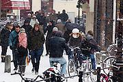 Op de Donkere Gaard in Utrecht lopen en fietsen mensen door de sneeuw om Sinterklaasinkopen te doen.<br /> <br /> Cyclists and pedestrians in the snow at the Donkere Gaard Utrecht.