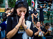 13 OCTOBER - BANGKOK, THAILAND: A woman prays while she waits for Buddhist monks on the first anniversary of the death of Bhumibol Adulyadej, the Late King of Thailand. About 199 monks from 14 Buddhist temples in Bangkok participated in the mass merit making at Siriraj Hospital to mark the anniversary of the revered King's death. He will be cremated on 26 October 2017.  PHOTO BY JACK KURTZ