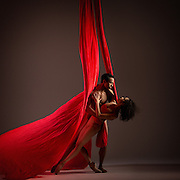Pax de duex of two contemporary ballet dancers from Dance Theatre of Harlem with red material. Shot in the studio against a dark background. Photographed by dance photographer, Rachel Neville.
